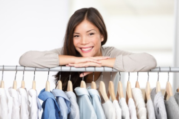 woman smiling over shirt rack