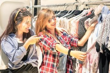 women looking at rack of clothes