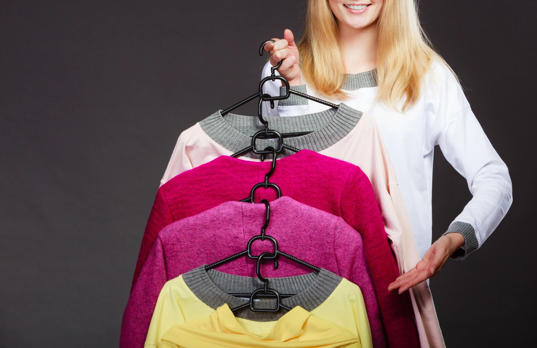 woman holding hangars of sweaters